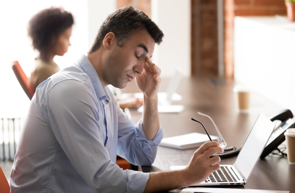 Man in front of a laptop rubbing his eyes because of digital eye strain.