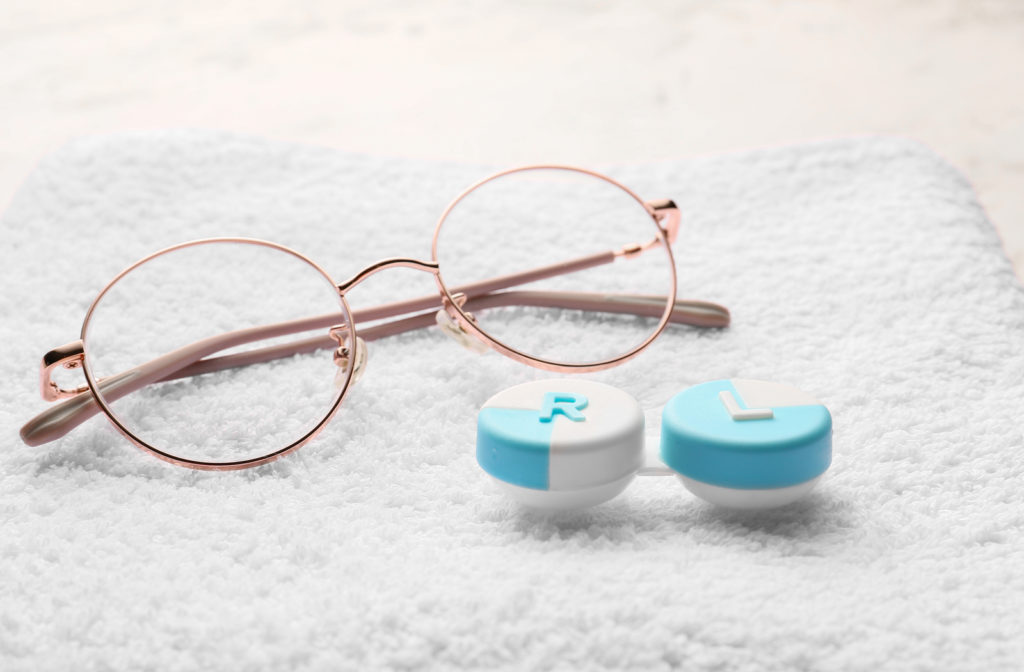 A pair of glasses and contact lens case sitting on a white towel.