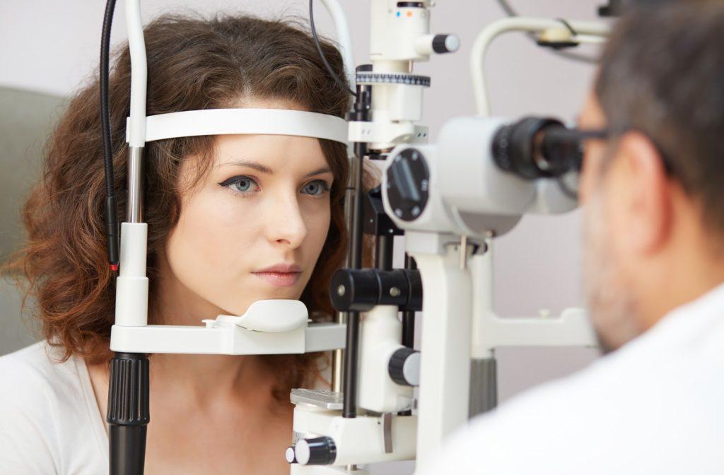 Young woman undergoing eye exam by her optometrist.