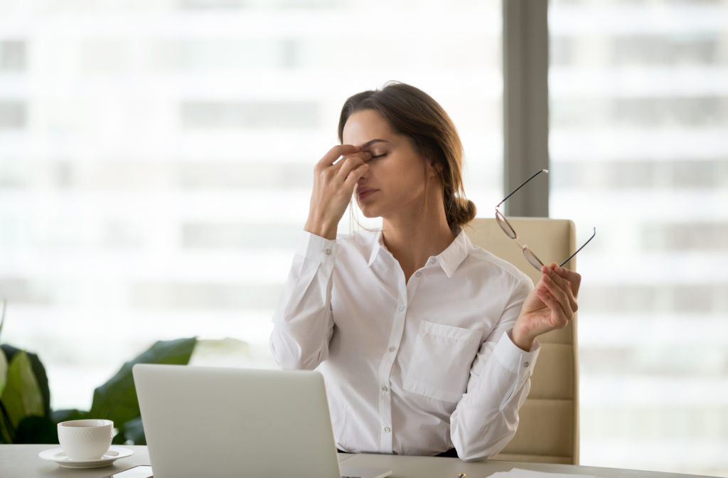 Woman frustrated due to dry eye while working on laptop